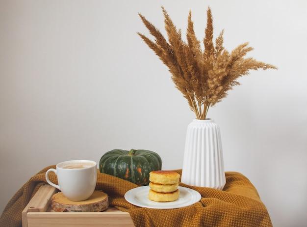 一杯のコーヒーカプチーノコテージチーズパンケーキ、黄色いマスタード色の格子縞、秋