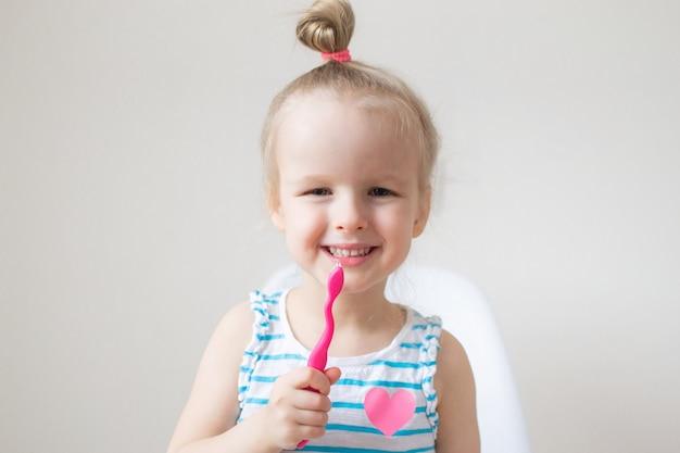 Счастливая маленькая девочка чистит зубы, розовая зубная щетка, гигиена полости рта, утренняя ночь