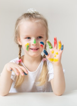 カラフルな手で白人の少女絵画家で早期塗装学校の就学前の開発の子供のゲームの準備