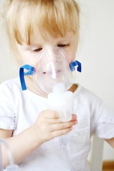 Маленькая девочка в маске для ингаляций, делая ингаляции с помощью небулайзера, дома ингалятор на столе, в помещении, больной ребенок