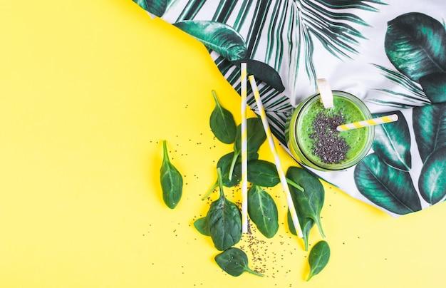 チア種子、健康食品のコンセプト、朝食、黄色の背景が付いている瓶に緑のほうれん草のスムージー