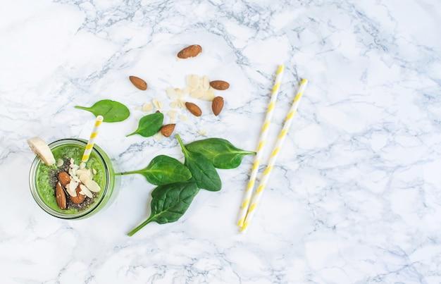 チア種子、アーモンドナッツ、健康食品のコンセプトが付いている瓶に緑のほうれん草のスムージー