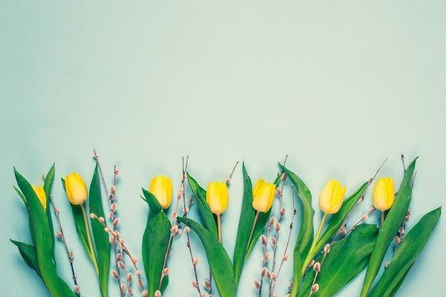 黄色のチューリップの花束、青い背景、春の時間。イースターの日の概念。上面図。コピースペース