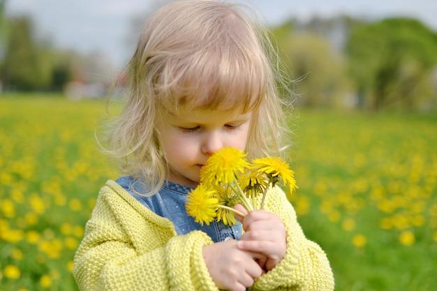 タンポポの花が付いている公園を歩いてかわいい女の子