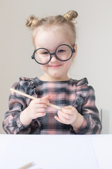 丸いメガネの白人少女。小さな先生。面白いメガネユーモア。レトロなスタイル