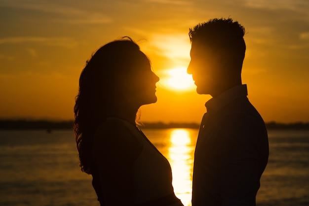 Пара силуэтов на пляже на закате