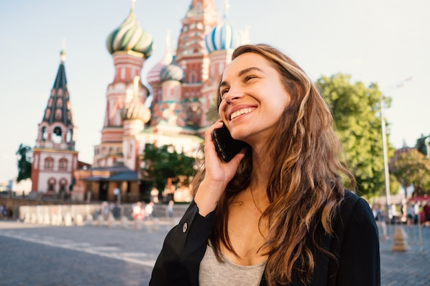 背景に聖ワシリイ大聖堂と、電話で話している赤の広場で笑顔の若い女性の肖像画。ロシアのモスクワ。