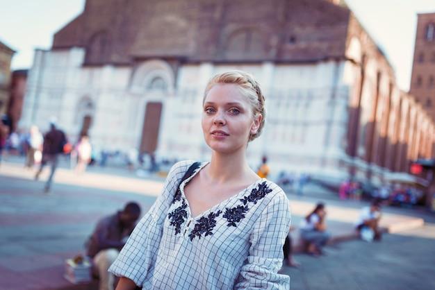 ボローニャ、イタリアで屋外笑顔若い金髪美人ライフスタイルの肖像画。サンペトロニオ大聖堂