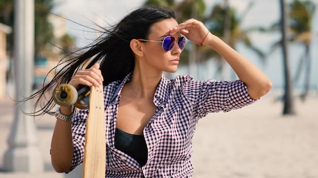 フロリダ州マイアミのハリウッドビーチにロングボードを持つ美しい若い女性の肖像画。フィルター処理された画像