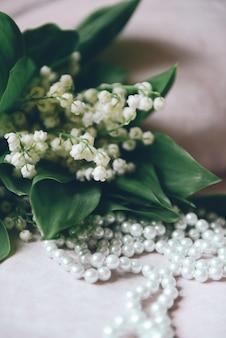インテリアの谷間の花束のユリと真珠ビーズ