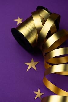 Золотая праздничная лента на фиолетовой матовой поверхности