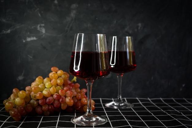ピンクのブドウの房と赤ワインのグラス