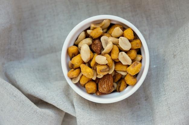 Закуски, соленые орехи в горшочке из белой глины на льняной ткани