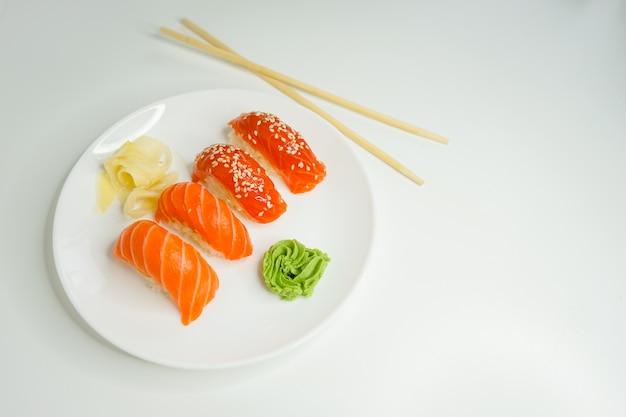 Японские суши с лососем и кунжутом на белой тарелке