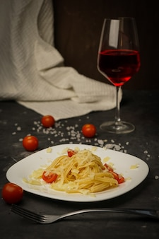 チェリートマトと暗闇の上の皿にイタリアのパスタ