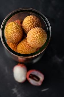 Селективный фокус, тропические ягоды личи в стеклянной банке на темной поверхности
