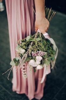 ピンクのウェディングドレスと結婚指輪の花の花束と幸せと笑顔の女性