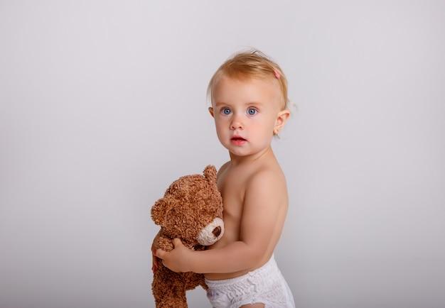 白のテディベアと遊ぶおむつの女の赤ちゃん