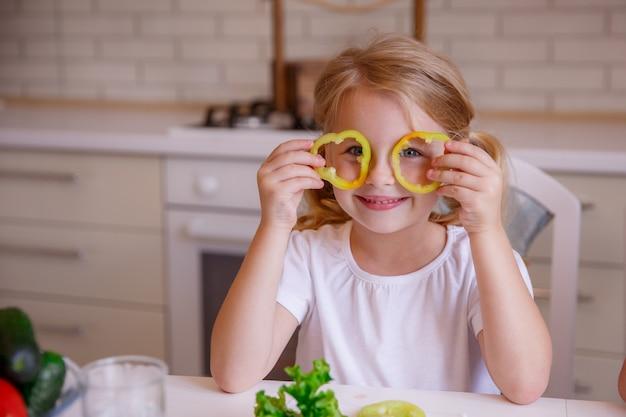Белокурая девочка играет с перцем на кухне