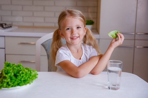 Белокурая девочка ест овощи на кухне