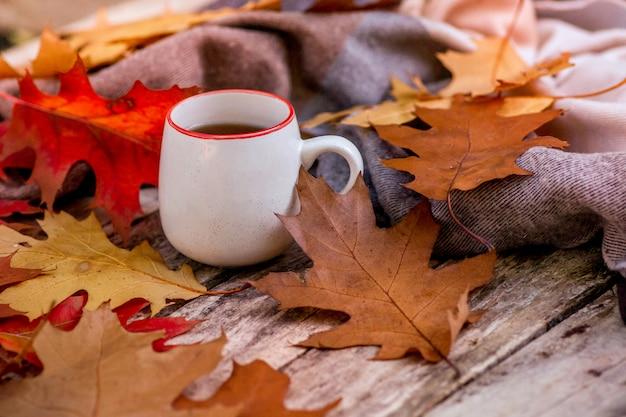 ティーカップ、紅葉と秋の風景。明るい紅葉と感謝祭の素朴なテーブル