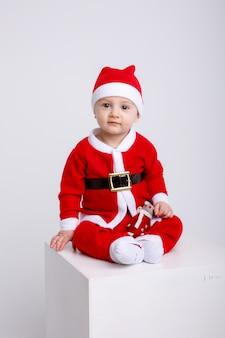 白い背景に白い立方体の上に座ってサンタ衣装で小さな男の子