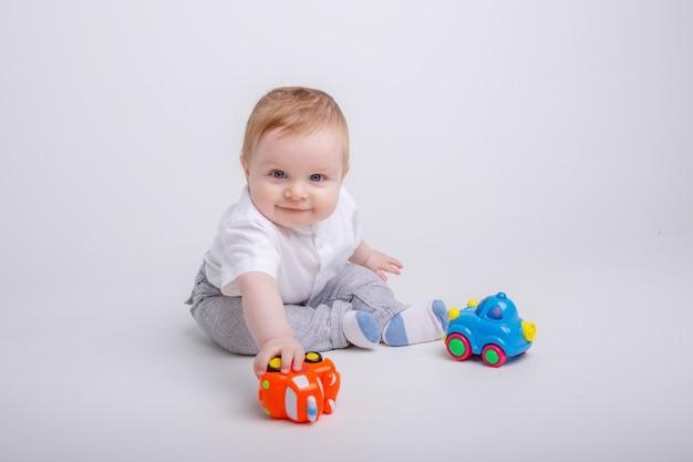 Мальчик играет с игрушечными машинками на белом фоне