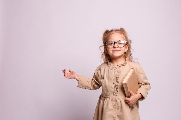 Улыбается маленькая школьница девушка в очках с книгой на сером фоне. место для текста, баннер