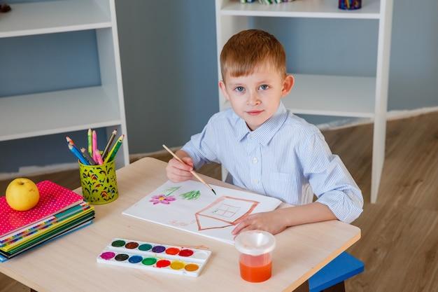 Школьник рисует дома за столом. концепция образования