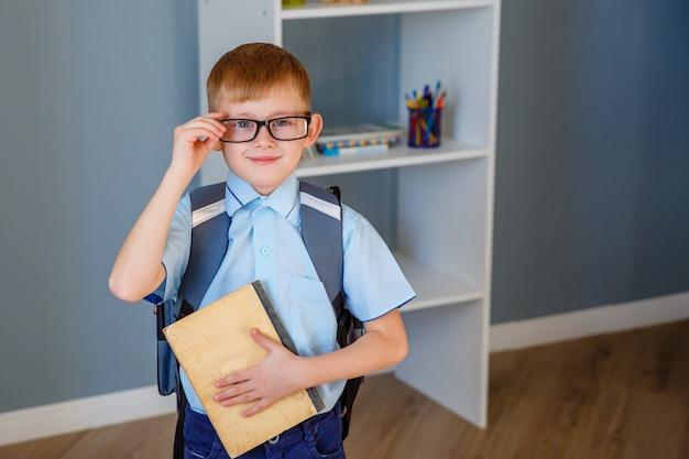 バッグ、本、リンゴを手に持つメガネの小さな男子生徒。トレーニングと教育の概念