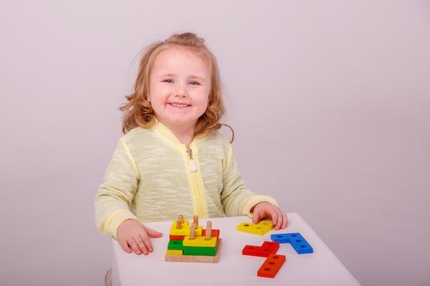 Маленькая милая блондинка играет в конструкторе. концепция дошкольного образования