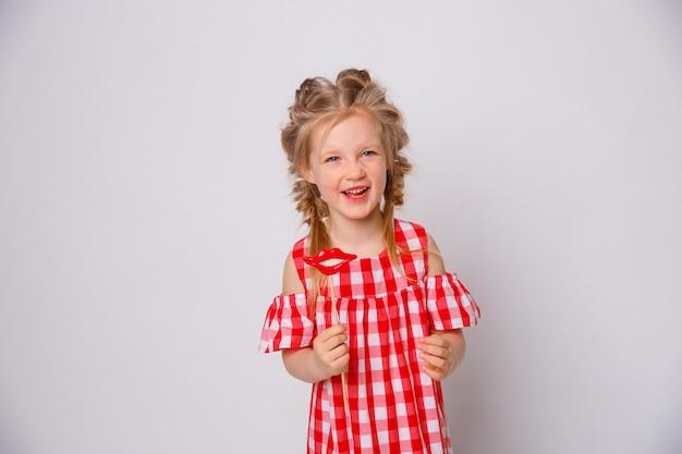 Смешное усмехаясь платье лета ребёнка на белой предпосылке. девочка с губным аксессуаром на палочке.
