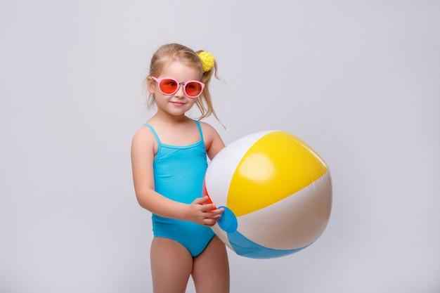 Милая улыбающаяся маленькая девочка в купальнике с резиновым кольцом на белом