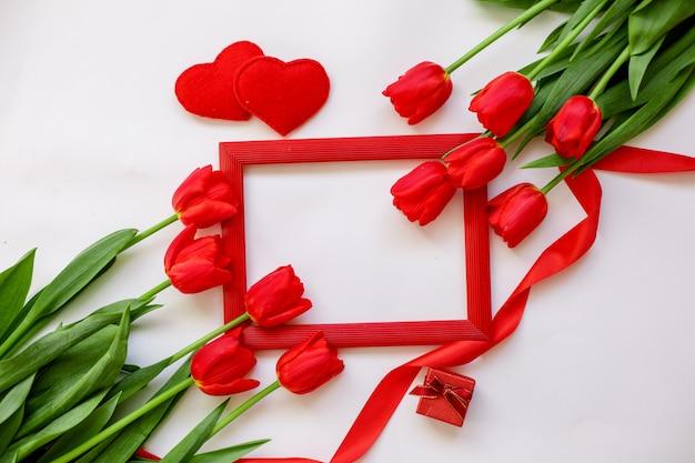 フレームと白い背景で隔離赤いチューリップの背景。テキストのためのスペース。バレンタインデー、国際女性デーのコンセプト