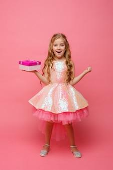 Маленькая девочка с подарком в руках улыбается на розовом пространстве.