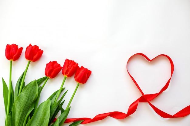 赤いチューリップとリボンハート。バレンタインデー、母の日、結婚式、女性の日のコンセプト
