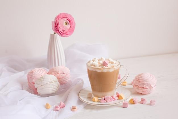 ピンクのおはようカード。一杯のコーヒー、マシュマロ、明るい木製の空間にピンクの花。