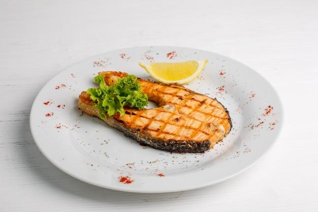 Стейк из лосося на гриле с лимоном на белой тарелке
