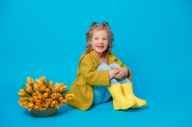 青色の背景に春の花の花束と黄色のブーツの少女