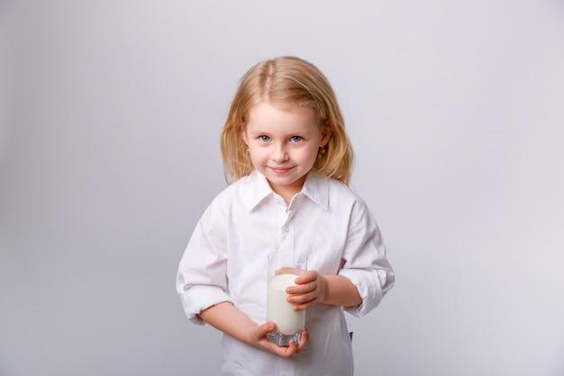 ミルクのガラスと小さな幸せな女の子