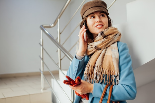 コートを着た女性実業家がスマートフォンでショッピングモールの階段の上に立ちます。ショッピング。ファッション