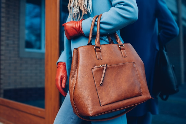 美しさとファッション茶色のバッグハンドバッグを保持しているコートと手袋を身に着けているスタイリッシュなおしゃれな女性