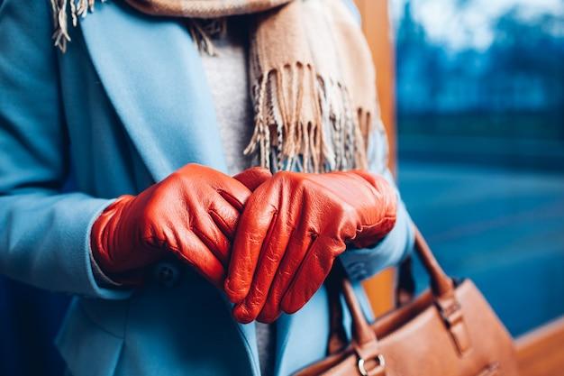 エレガントな衣装。コート、スカーフ、茶色の手袋でスタイリッシュな女性のクローズアップ。