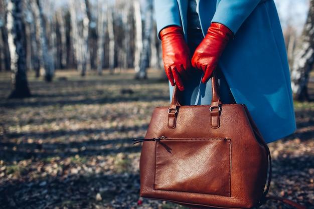 美しさとファッション茶色のバッグのハンドバッグを保持している明るいドレスを着ているスタイリッシュなおしゃれな女性