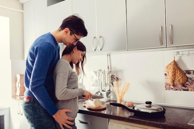 ハグと夕食を調理する台所で若いカップル。