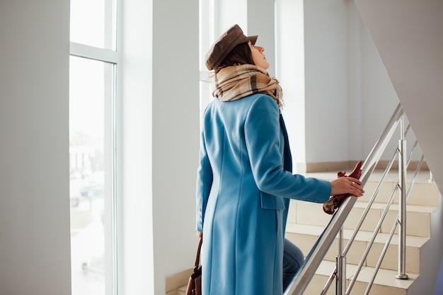コートを着たビジネスウーマンがモールの階段を登ります。ショッピング。ファッション