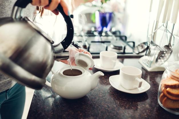 テーブルでセラミックカップにお茶を注ぐ女