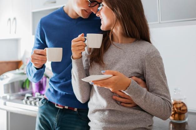 ハグと台所でお茶を飲む若いかわいいカップル