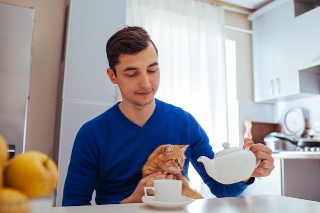 ハンサムな若い男の肖像は台所で猫とお茶を注ぐ