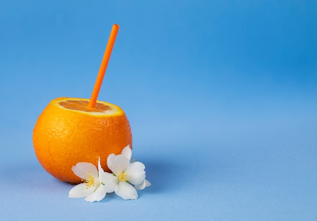 Свежий апельсин с соломой и цветами